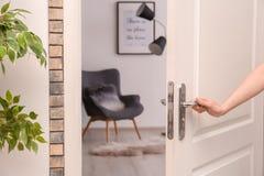 Öppningsdörr för ung kvinna till beautifully ordnat rum Royaltyfri Foto