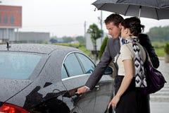 Öppningsdörr för ung man av bilen för kvinna Royaltyfria Foton