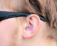 Örat av den unga mannen i hörapparaten arkivfoton