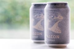 Örebro Sweden 15 october 2017 ice cold falcon beer cans. Örebro Sweden 15 october 2017 two ice cold falcon beer cans standing on a bench in window light stock image