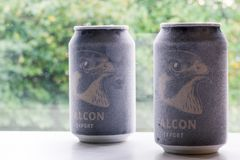 Örebro Sweden 15 october 2017 ice cold falcon beer cans. Örebro Sweden 15 october 2017 two ice cold falcon beer cans standing on a bench in window light royalty free stock images