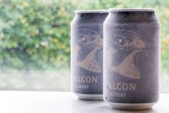 Örebro Sweden 15 october 2017 ice cold falcon beer cans. Örebro Sweden 15 october 2017 two ice cold falcon beer cans standing on a bench in window light royalty free stock image