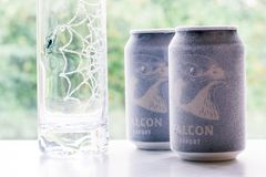 Örebro Sweden 15 october 2017 ice cold falcon beer cans. Örebro Sweden 15 october 2017 two ice cold falcon beer cans standing on a bench in window light royalty free stock photo