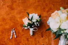 Örhängen för brud` s, boutonniere och brud- bukett på lantlig träbakgrund Fotografering för Bildbyråer