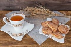Öron av vete, en kopp te och kex på en träbakgrund royaltyfria foton