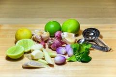 Ört för matingrediens limefrukt, citrongräs, vitlök, schalottenlökar och kaffirlimefruktblad på träbakgrund royaltyfri fotografi