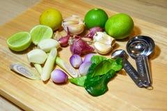 Ört för matingrediens limefrukt, citrongräs, vitlök, schalottenlökar och kaffirlimefruktblad på träbakgrund royaltyfri foto