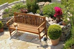 Örtagård och bänk med det lilla äppleträdet Royaltyfri Bild