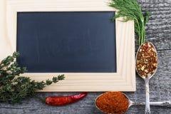 Örter, chili, antika metallskedar med kryddor och svart krita b arkivfoton