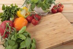 Örter och grönsaker med en tom skärbräda Fotografering för Bildbyråer