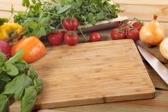 Örter och grönsaker med en tom skärbräda Arkivbilder