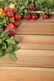 Örter och grönsaker med ett tomt träbräde Arkivfoton