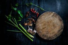 Örter och kryddor runt om tom skärbräda på mörk stenbackgr Royaltyfria Foton