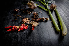 Örter och kryddor runt om tom skärbräda på mörk stenbackgr Arkivbild