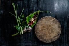 Örter och kryddor runt om tom skärbräda på mörk stenbackgr Arkivbilder