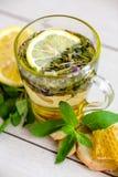 Örtte i ett exponeringsglas rånar med citronen och honung på en ljus bakgrund fotografering för bildbyråer