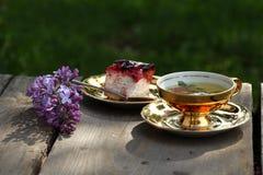 Örtte i guld- kopp, ostkaka med svart vinbärtoppning och lilalila royaltyfria bilder