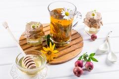 Örtte med örter och blommor i ett glass te lägger in med honung Bukett av blommor Royaltyfri Bild