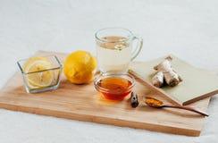 Örtte med kamomillblommor, gurkmeja och honung på ett träbräde Behandling av den varma drinkingefäran Folk boter Royaltyfri Bild