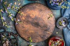 Örttebakgrund med det runda träbrädet, kopp te och olika blommor och läkaörter på mörk bakgrund, bästa sikt, fram Arkivfoto