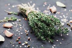 Örttimjan och kryddor på den svarta köksbordcloseupen Royaltyfri Bild