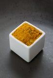 Österlänningen kryddar den växt- blandningen på mörk keramisk maträtt Arkivfoton