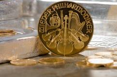 Österreich-Goldphilharmonische Münze mit Silberbarren im Hintergrund Lizenzfreie Stockbilder