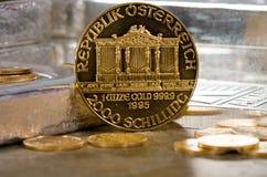 Österreich-Goldphilharmonische Münze mit Silberbarren im Hintergrund Stockbild