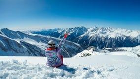 Österreich - Snowboardingmädchen, das auf dem Schnee, die Ansicht genießend sitzt lizenzfreie stockbilder