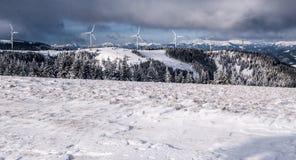 Österreichische Alpen des Winters mit Windkraftanlagen und Spitzen Lizenzfreie Stockbilder