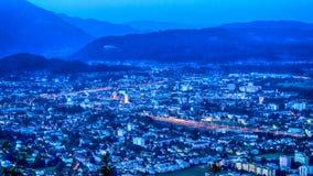 Österreichische Stadt und Berge bis zum Nacht stockfotos