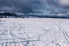 Österreichisches Alpenpanorama des Winters mit Windkraftanlagen und blauem Himmel mit Wolken Stockfoto