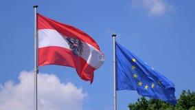 Österrike och EU-flagga som fladdrar mot en blå molnig himmel lager videofilmer