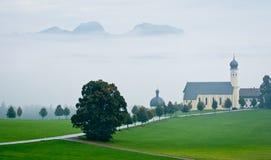 Österrikiskt landskap med kyrkan i dåligt väder Royaltyfria Foton