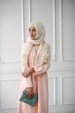 Östlig flicka i en härlig ljus muslimsk klänning, en sjal på hennes huvud på en ljus klassisk bakgrund Royaltyfri Fotografi
