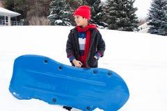 Östlig indisk pojke som toboganning i snowen Arkivbilder