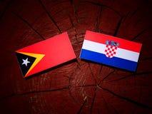 Östlig timoresisk flagga med den kroatiska flaggan på en trädstubbe Royaltyfri Fotografi