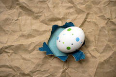 Östligt ägg i brunt inpackningspapper för hål arkivfoton