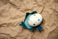 Östligt ägg i brunt inpackningspapper för hål royaltyfria foton