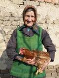 Östligt - europeisk gammal höna för bondekvinnainnehav royaltyfri bild