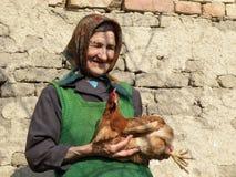 Östligt - europeisk gammal höna för bondekvinnainnehav fotografering för bildbyråer
