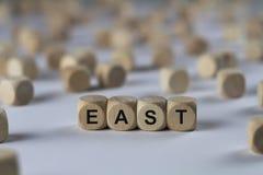 Östligt - kub med bokstäver, tecken med träkuber fotografering för bildbyråer