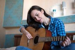 Östligt kvinnasammanträde för brunett på hennes säng i den hållande gitarren för sovrum som komponerar en sång - musiker, låtskri fotografering för bildbyråer