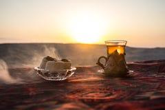 Östligt svart te i exponeringsglas på en östlig matta Östligt tebegrepp Armudu traditionell kopp baltisk havssolnedgång för bakgr royaltyfri bild