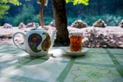 Östligt svart te i exponeringsglas på en östlig matta Östligt tebegrepp Armudu traditionell kopp baltisk havssolnedgång för bakgr arkivfoton
