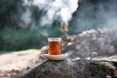 Östligt svart te i exponeringsglas på en östlig matta Östligt tebegrepp Armudu traditionell kopp baltisk havssolnedgång för bakgr royaltyfria foton