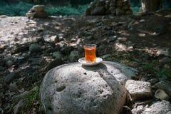 Östligt svart te i exponeringsglas på en östlig matta Östligt tebegrepp Armudu traditionell kopp baltisk havssolnedgång för bakgr royaltyfri fotografi