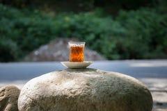Östligt svart te i exponeringsglas på en östlig matta Östligt tebegrepp Armudu traditionell kopp baltisk havssolnedgång för bakgr arkivfoto