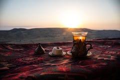 Östligt svart te i exponeringsglas på en östlig matta Östligt tebegrepp Armudu traditionell kopp baltisk havssolnedgång för bakgr royaltyfri foto