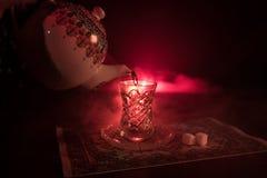 Östligt te i traditionell glasse och kruka på svart bakgrund med ljus och rök Östligt tebegrepp Armudu traditionella Azerb royaltyfria bilder